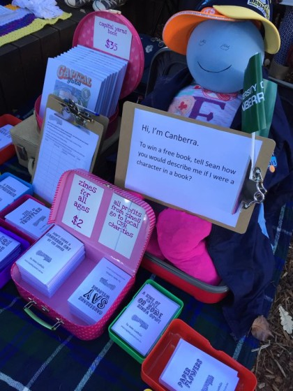 Picture of zines inside lunchboxes and a large Canberra doll at Suitcase rummage